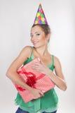 Femme de brune dans des présents d'une exploitation de chapeau d'anniversaire Images libres de droits