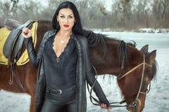 Femme de brune dans la position noire de costume près du cheval photos libres de droits
