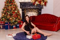 Femme de brune dans la robe noire courte se reposant sur le tapis près de l'arbre de Noël Jeune femme riante Belle femelle photographie stock
