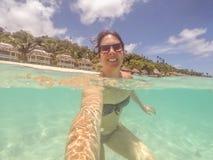 Femme de brune dans le bikini et des lunettes de soleil nageant prenant un selfie Photographie stock libre de droits