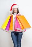 Femme de brune dans le chapeau de Santa retenant des sacs ? provisions Image libre de droits