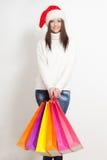 Femme de brune dans le chapeau de Santa retenant des sacs ? provisions Photographie stock