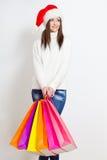 Femme de brune dans le chapeau de Santa retenant des sacs ? provisions Photo libre de droits
