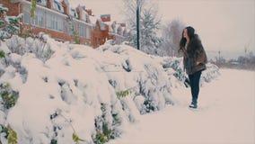Femme de brune dans le manteau de fourrure souriant sur le fond des bâtiments sur la rue d'hiver Mouvement lent banque de vidéos