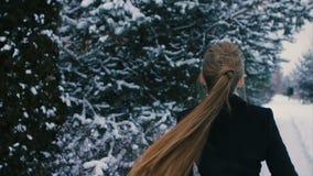Femme de brune dans le manteau noir tournant autour d'elle-même le mouvement lent banque de vidéos