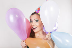 Femme de brune dans un chapeau d'anniversaire tenant des ballons et le sourire Image libre de droits