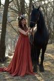 Femme de brune dans une robe rouge avec une guirlande des fleurs Photo stock