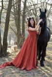 Femme de brune dans une robe rouge avec une guirlande des fleurs Image stock
