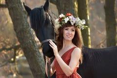 Femme de brune dans une robe rouge avec une guirlande des fleurs Image libre de droits