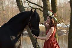 Femme de brune dans une robe rouge avec une guirlande des fleurs Photographie stock libre de droits