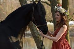 Femme de brune dans une robe rouge avec une guirlande des fleurs Photos libres de droits