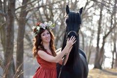 Femme de brune dans une robe rouge avec une guirlande des fleurs Photo libre de droits