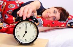 Femme de brune dormant dans sa chambre à coucher avec le réveil Images stock