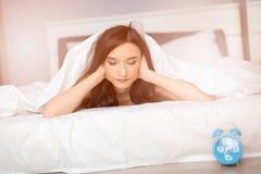 Femme de brune dormant sur son estomac couvert par la couverture de lit blanche Image stock