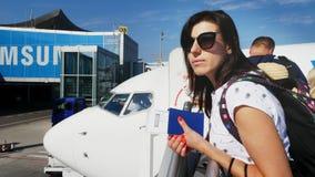 Femme de brune en verres de soleil, avec le sac à dos, tenant les billets de carte d'embarquement de ligne aérienne, et le passep clips vidéos
