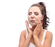 Femme de brune faisant la feuille faciale de masque Beauté et concept de soins de la peau Fille appliquant le masque à son visage Photo libre de droits