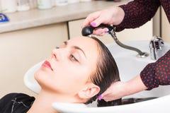 Femme de brune faisant laver des cheveux dans le salon Image libre de droits
