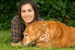 Femme de brune félicitant l'arrière-cour canine Gra de chien de golden retriever Image libre de droits