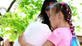 Femme de brune, lunettes de soleil de port, avec sa fille, fille de 8 années, avec les tresses bleus, mangeant le coton doux banque de vidéos