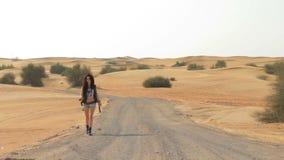 Femme de brune marchant sur la route de désert banque de vidéos
