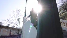 Femme de brune marchant vers le haut des escaliers sur Broadway ensoleillé banque de vidéos