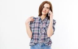Femme de brune parlant sur le smartphone au-dessus du fond d'isolement se dirigeant avec des doigts sur l'espace de copie, signe  photographie stock