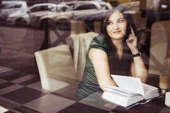 Femme de brune s'asseyant au café de livre de lecture de café, studing et de boissons et parlant au téléphone Images libres de droits