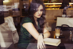 Femme de brune s'asseyant au café de livre de lecture de café, studing et de boissons et attendant quelqu'un qui est en retard Photo libre de droits