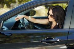 Femme de brune s'asseyant dans la voiture, beau conducteur féminin sexy Image libre de droits