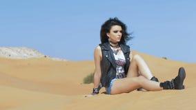 Femme de brune s'asseyant dans le désert banque de vidéos