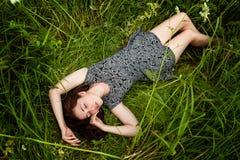 Femme de brune se trouvant sur l'herbe verte photo stock