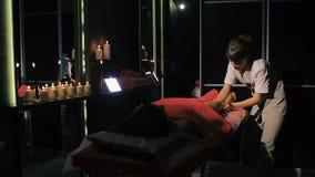 Femme de brune se trouvant sur la table de massage dans le salon de beauté, alors que le thérapeute professionnel encaisse le mas banque de vidéos