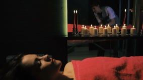 Femme de brune se trouvant sur la table de massage dans le salon de beauté, alors que le thérapeute professionnel fait le massage banque de vidéos