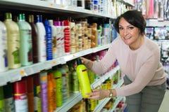Femme de brune sélectionnant des produits de soins capillaires Photos libres de droits