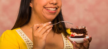Femme de brune tenant le petit plat du gâteau de chocolat avec le remplissage crème, morsure de saisie utilisant la fourchette, m photographie stock