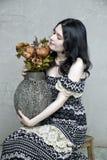 Femme de brune tenant le vase à vintage de fleurs Photo libre de droits