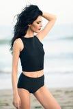 Femme de brune utilisant le dessus et les culottes noirs près d'une plage Photos libres de droits