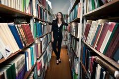 Femme de Brunette à la bibliothèque images stock