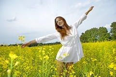 Femme de Brunette dans un domaine de fleurs jaune photos stock