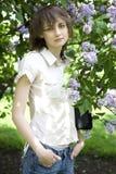 Femme de Brunnete restant le lilas avoisinant Photos stock