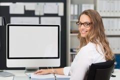 Femme de bureau à sa table de travail avec l'ordinateur Images stock