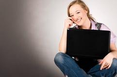 Femme de bureau avec l'ordinateur portatif Photographie stock libre de droits