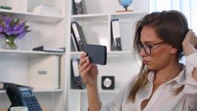Femme de bureau fixant ses cheveux utilisant le smartphone comme miroir Photos stock
