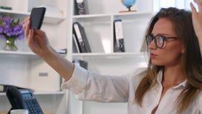 Femme de bureau fixant ses cheveux utilisant le smartphone comme miroir Photos libres de droits