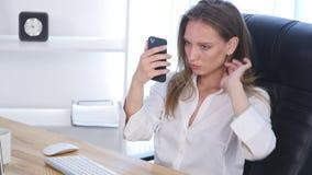 Femme de bureau fixant ses cheveux utilisant le smartphone comme miroir Photographie stock libre de droits