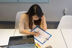 Femme de bureau vérifiant des données dans le diagramme avec le collègue photo stock