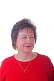 Femme de C.C en rouge avec le collier d'or souriant au côté Image stock