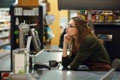 Femme de caissier sur l'espace de travail dans le supermarché Images stock