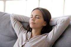 Femme de calme mettant des mains derrière la tête se reposant sur le divan confortable photo libre de droits