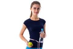 Femme de centimètre autour de sa taille tenant la pomme et l'eau Images libres de droits